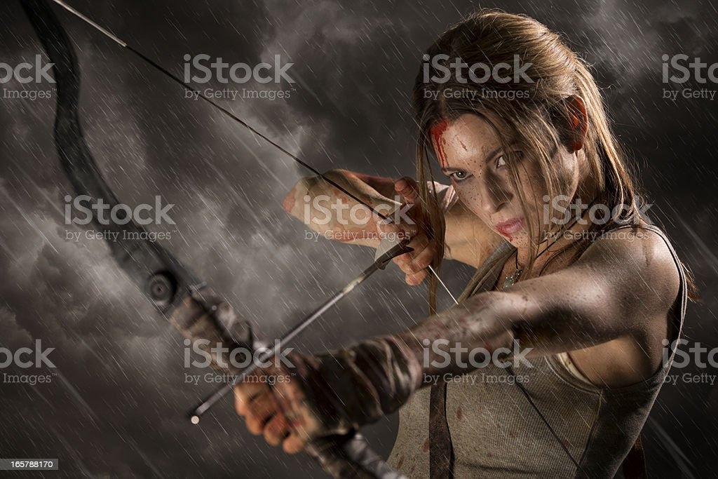 Female heroine with bow and arrow on a rainy night stock photo