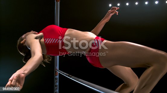 Female high jumper jumping over the bar against black background.