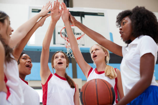 Female High School Basketball Players Joining Hands During Team Talk With Coach Female High School Basketball Players Joining Hands During Team Talk With Coach basketball sport stock pictures, royalty-free photos & images