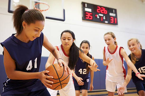 Female High School Basketball Team Playing Game Female High School Basketball Team Playing Game In The Gym basketball sport stock pictures, royalty-free photos & images