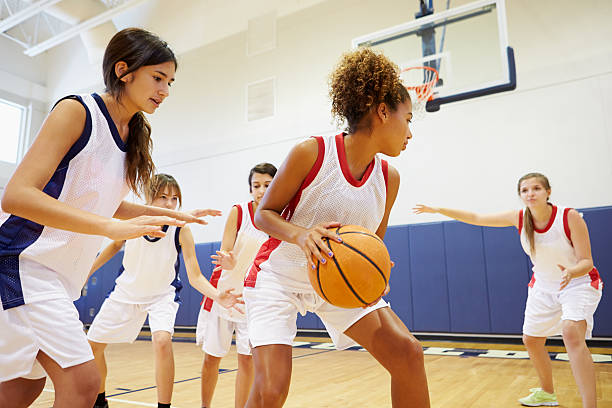 Female High School Basketball Team Playing Game Female High School Basketball Team Playing Game In Gymnasium female high school student stock pictures, royalty-free photos & images