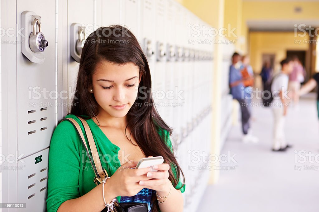 Female High School Student By Lockers Using Mobile Phone stock photo