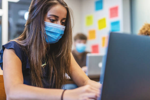 Female High School Student in Classroom Setting Wearing Mask stock photo