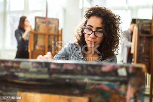 istock Female high school student making her painting on a class at art studio. 1077181958