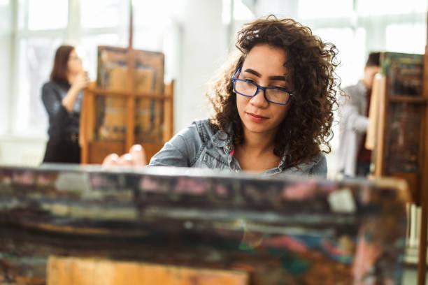 weibliche high-school-schüler machen ihre malerei auf einer klasse im art studio. - high school bilder stock-fotos und bilder