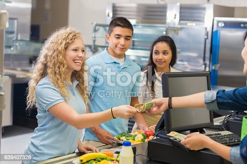 istock Female high school student pays cashier in cafeteria 639407326