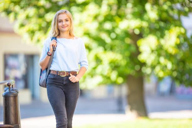 Weibliche Gymnasiastin mit Schultasche. Porträt von attraktiven jungen blonden Mädchen. – Foto