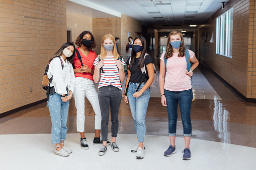 High school students and teenager girls go back to school in the classroom at their high school. They are required to wear face masks and practice social distancing during the COVID-19 pandemic. They value their education and are excited to be in school.