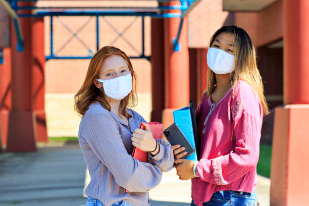 Female high school students attending school with face masks stock photo