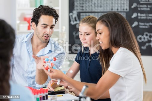 istock Female high school students examine atomic structure 877033900