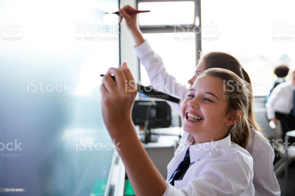 Female High School Students Wearing Uniform Using Interactive Whiteboard During Lesson royalty-free stock photo