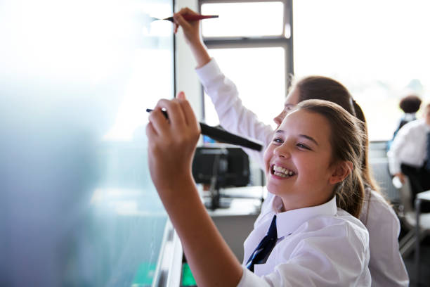 Female High School Students Wearing Uniform Using Interactive Whiteboard During Lesson Female High School Students Wearing Uniform Using Interactive Whiteboard During Lesson 12 13 years stock pictures, royalty-free photos & images