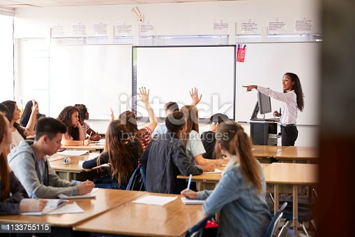 1160928955 istock photo Female High School Teacher Asking Question Standing By Interactive Whiteboard Teaching Lesson 1133755115
