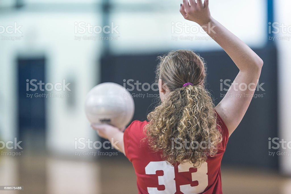 Female high school volleyball player serving during a match stock photo