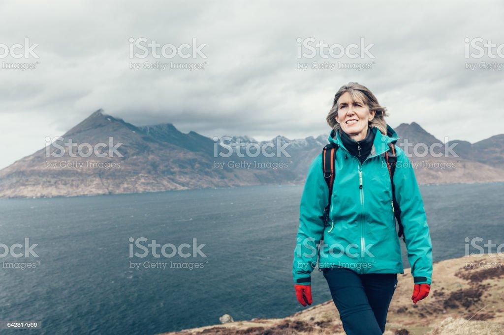 Female hiker 50-59years, walking on coastal trail in Skye, Scotland stock photo