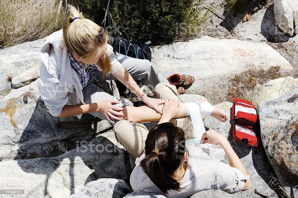 Female hiker aiding another injured female hiker stock photo