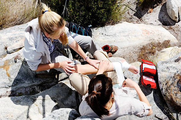 female hiker aiding another injured female hiker - first aid stock photos and pictures