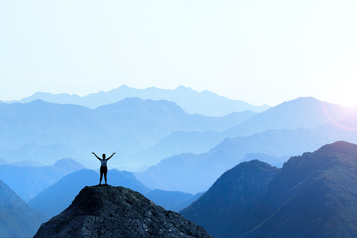 A female hiker stands on top of a rocky promontory and holds up her arms in celebration in front of a series of mountain ridges that seem to disappear into the distance as the haze obscures the details creating a graphic outline of the various layers of ridge lines.
