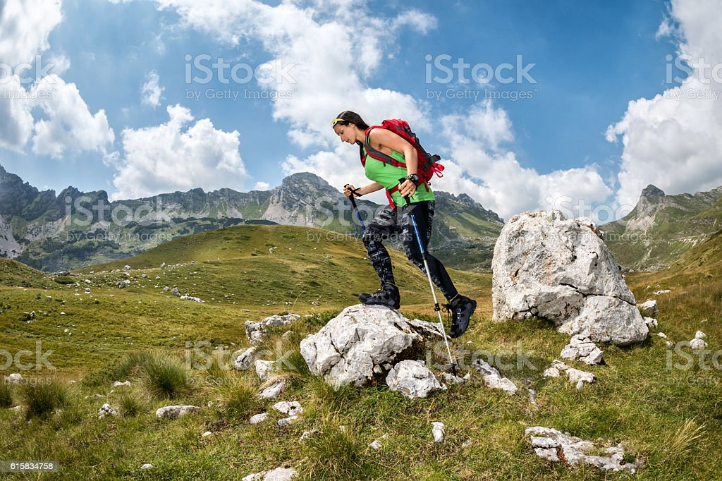 Female hiker climbing on the rock stock photo