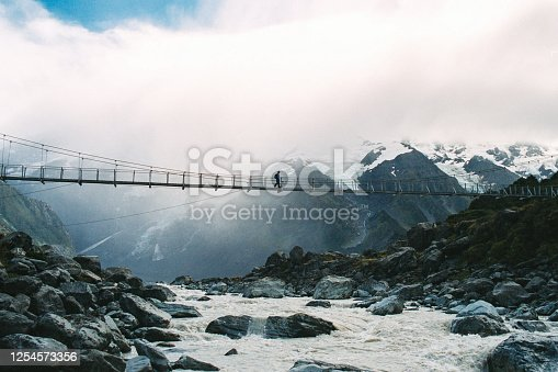 Female Hiker crossing a hanging suspension footbridge over a glacier river with snowcapped mountains and a glacier behind