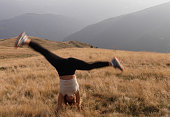 Female hiker does cartwheel on grassy hillside