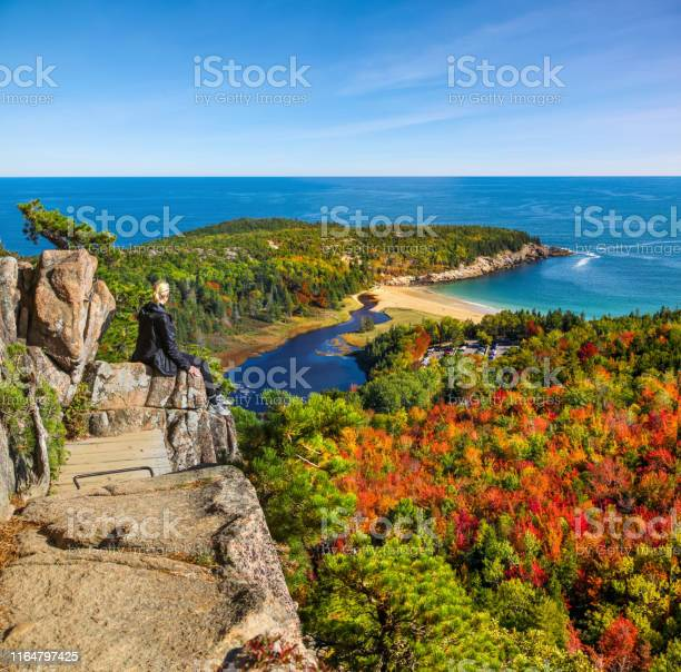 Photo of Female hiker enjoying the view from Beehive Trail in Acadia