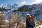 istock Female hiker exploring snow covered mountains, autumn 956844826