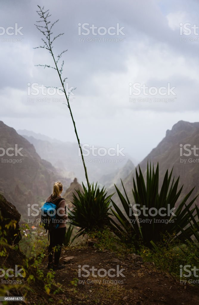 Female hiker in dusty mountain terrain enjoy spectacular view of sharp summits in the fog. Santo Antao Island Cape Verde - Royalty-free Adventure Stock Photo