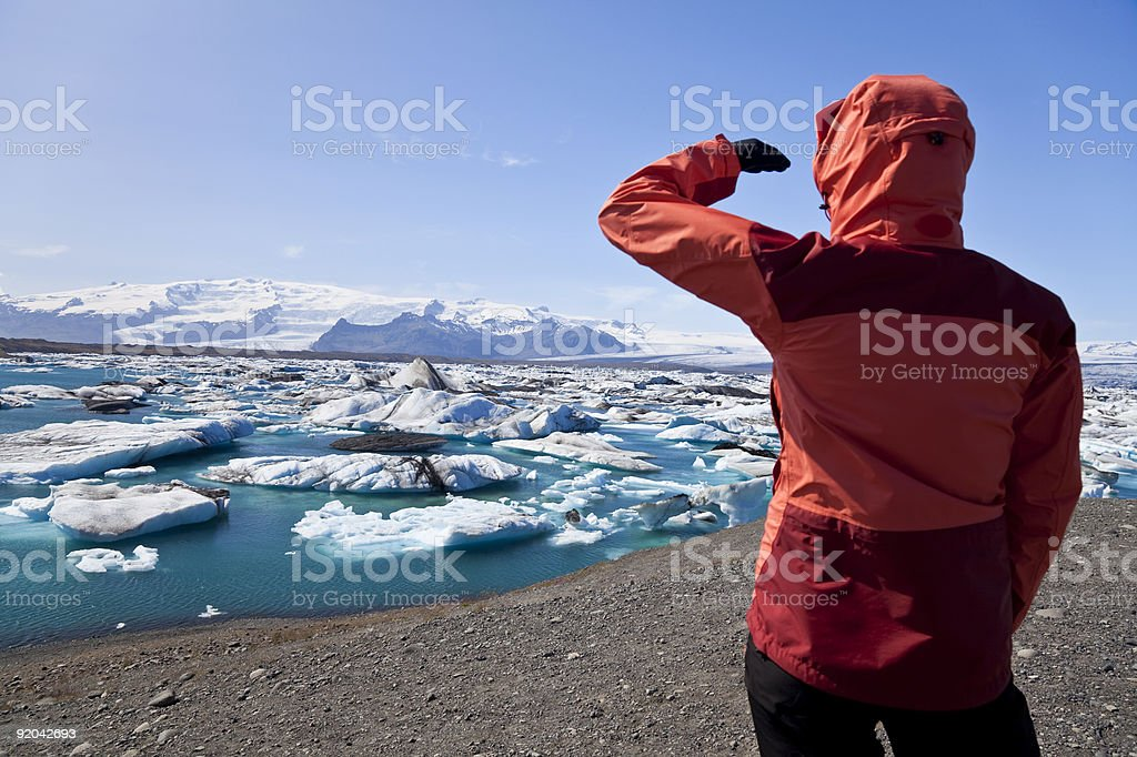 Female Hiker Looking at Iceberg Filled Lagoon, Jokulsarlon, Iceland stock photo