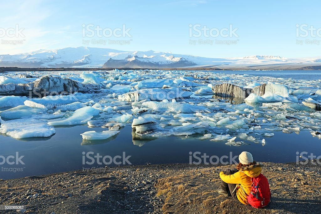 Female Hiker Looking at Icebergs at Jokulsarlon Glacial Lagoon Iceland stock photo
