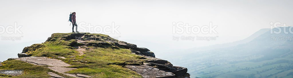 Female hiker looking at view from mountain summit panorama Wales stock photo