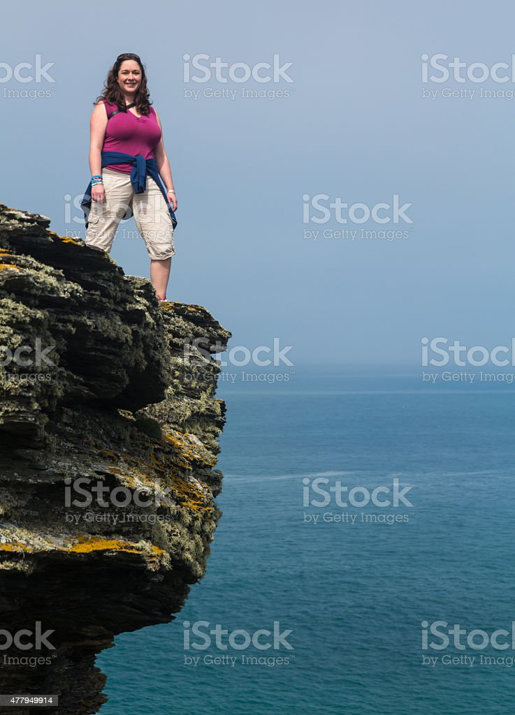 Female hiker on cliff edge near Tintagel Cornwall stock photo