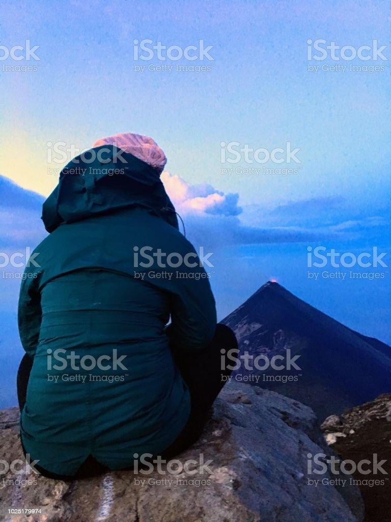 Une randonneuse Top of the world sur le sommet du Mont acatenango, un volcan en sommeil, avec vue sur Mont fuego, un volcan actif. - Photo