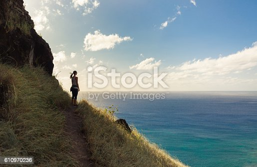 Female hiker overlooking the beautiful coast. (location Hawaii)