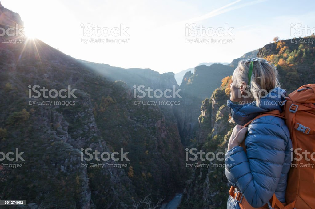 Female hiker pauses above mountain canyon at sunrise stock photo