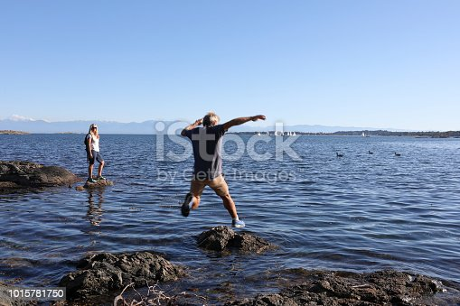 1083155024 istock photo Female hiker pauses on rocks, man leaps onto rock nearby 1015781750