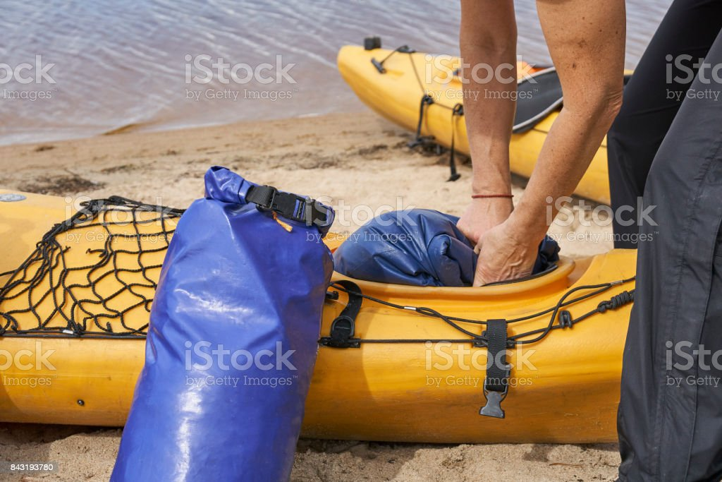 Female hiker puts a waterproof bag into the kayak stock photo
