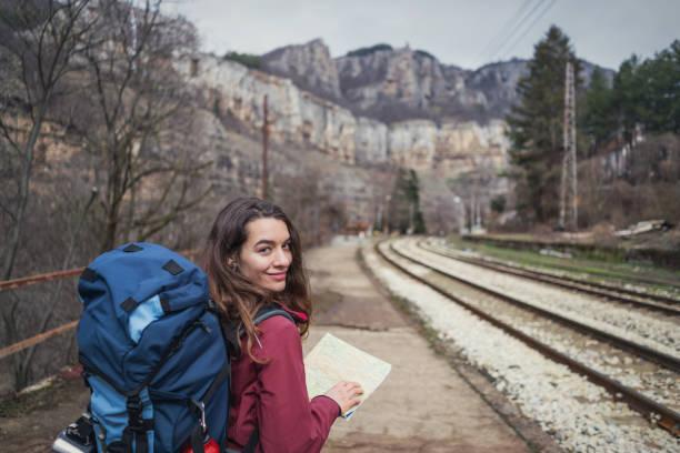 Female hiker reading travel map while walking along the railroad tracks stock photo