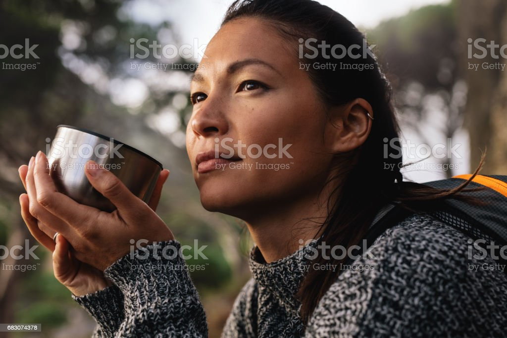Female hiker resting outdoors with a coffee stock photo