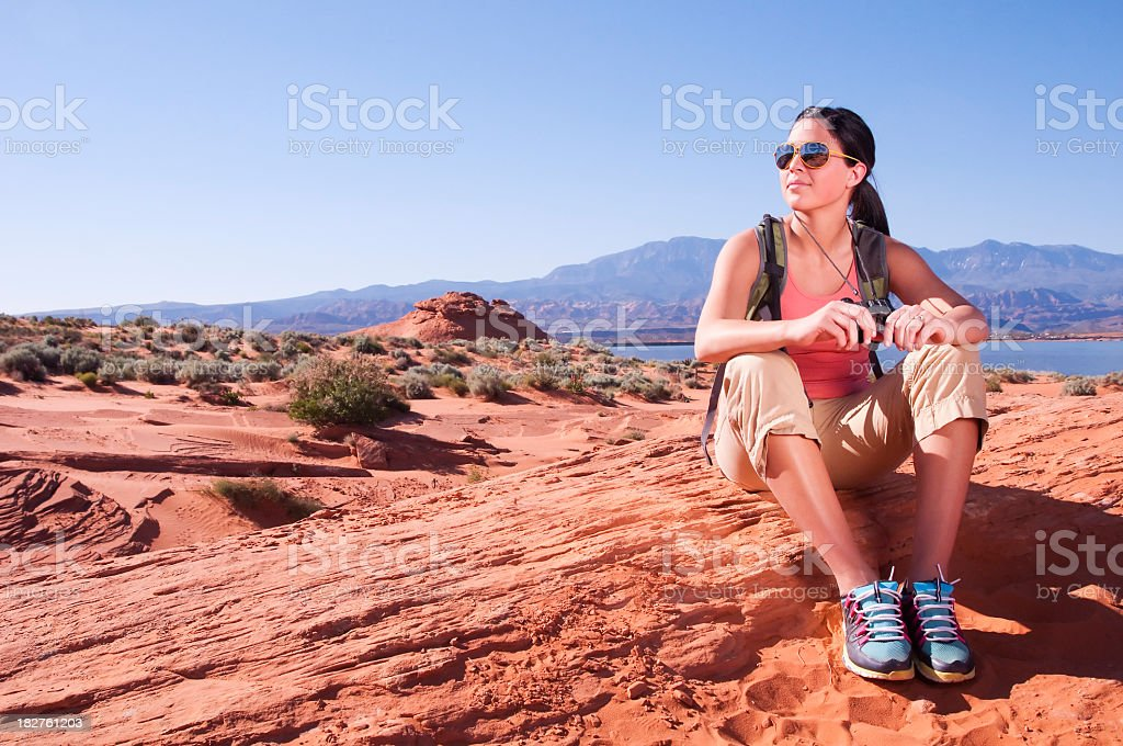 Female hiker rests in desert hill with lake in background stock photo