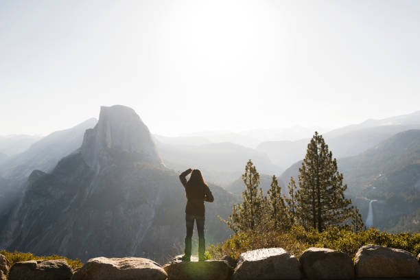Female hiker standing on a rock at a viewpoint towards Half Dome Park taking in the breathtaking view stock photo