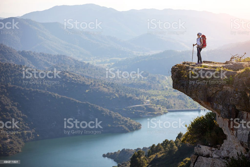 Female hiker standing on cliff stock photo