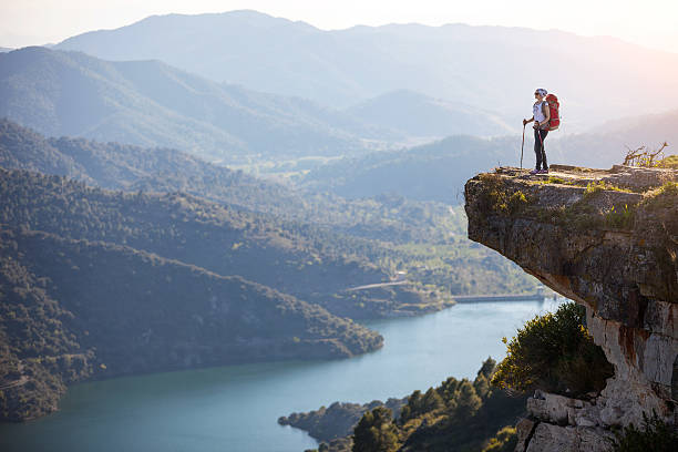 female hiker standing on cliff - cliff stock pictures, royalty-free photos & images