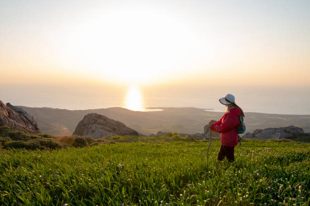 Female hiker stands in meadow and looks out to sea stock photo
