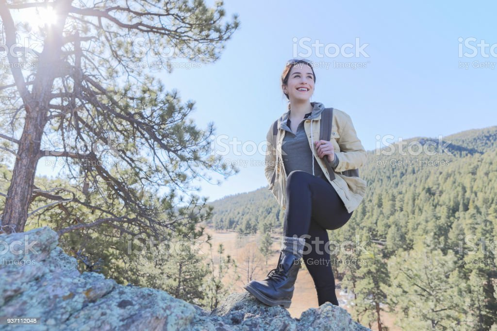 Female hiker stops to rest while on mountain trail stock photo