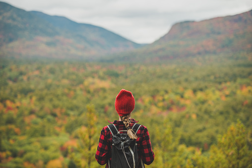 Female hiker in the mountains on a fall day with vibrant fall trees.