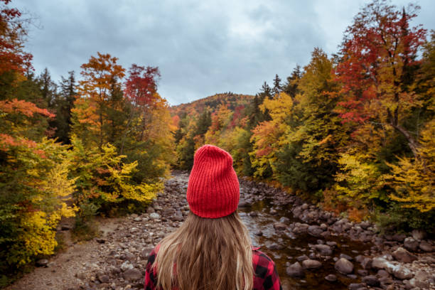 Female hiker surrounded by beautiful fall colors stock photo