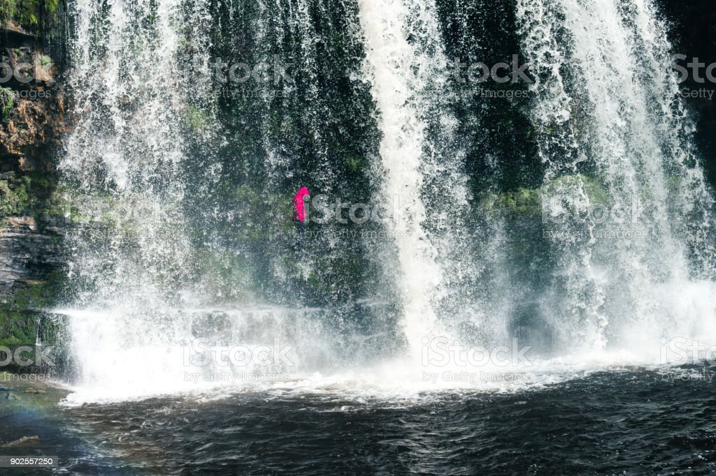 Female hiker, tourist, model standing or walking under the Sgwd Yr Eira Waterfall in Wales stock photo