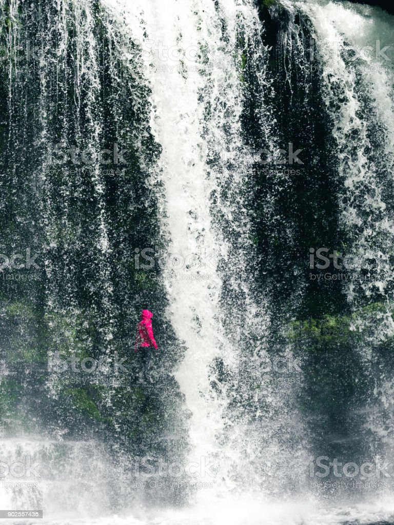 Female hiker, tourist, model standing or walking under the Sgwd Yr Eira Waterfall in Wales. In Portrait framing. stock photo