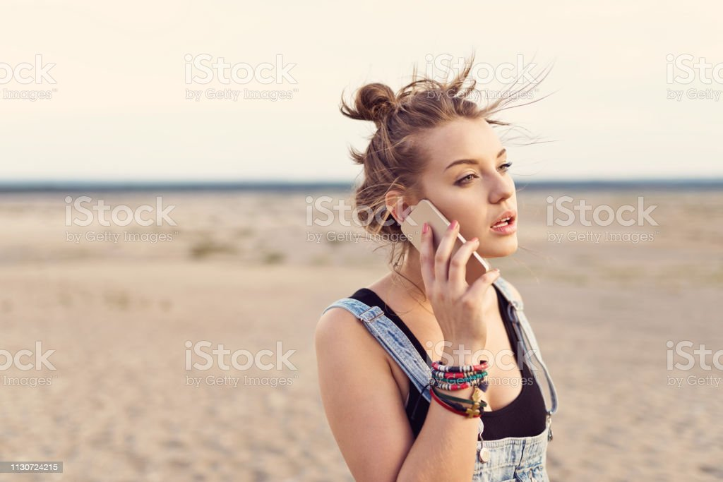 Female hiker using mobile phone at desert Female hiker using mobile phone at desert. Beautiful woman is looking away while standing on sandy landscape. She is enjoying her vacation. 20-24 Years Stock Photo